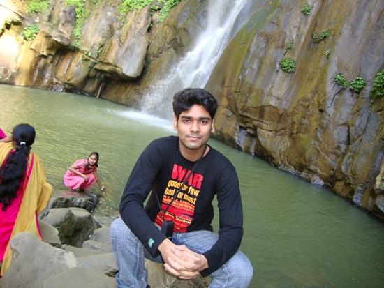 Tamal Anwar sitting next to the water falls